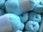 balls of bright light blue wool with a crinkle in it