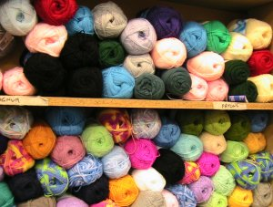 two shelves of balls of yarn in different colours